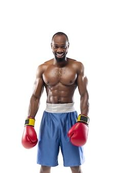 笑顔。白い壁に隔離されたプロのアフリカ系アメリカ人ボクサーの面白い、明るい感情。ゲームの興奮、人間の感情、顔の表情、スポーツコンセプトへの情熱。