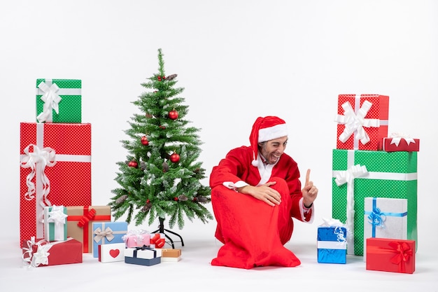 Smiling funny excited young man dressed as santa claus with gifts and decorated christmas tree sitting on the ground pointing above on white background