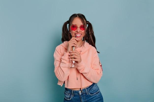 Улыбающаяся смешная девушка со счастливыми эмоциями наслаждается временем во время фотосессии в студии в круглых хрюмовых очках и розовом пуловере