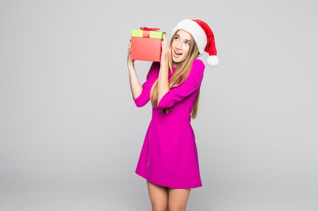 短いピンクのドレスと新年の帽子で面白い幸せな女性の笑顔は彼女の手で紙箱の驚きを保持