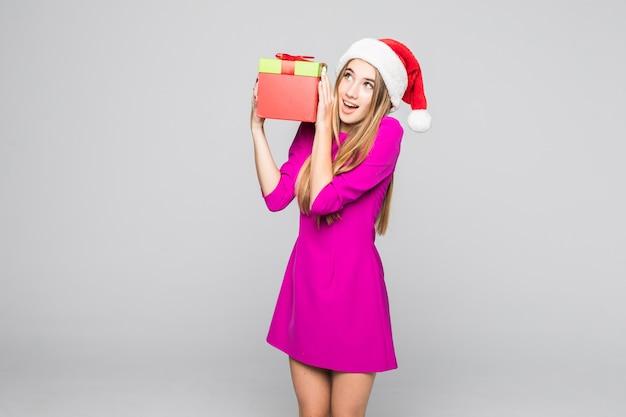 La signora felice divertente sorridente in breve vestito rosa e cappello del nuovo anno tiene la sorpresa della scatola di carta nelle sue mani