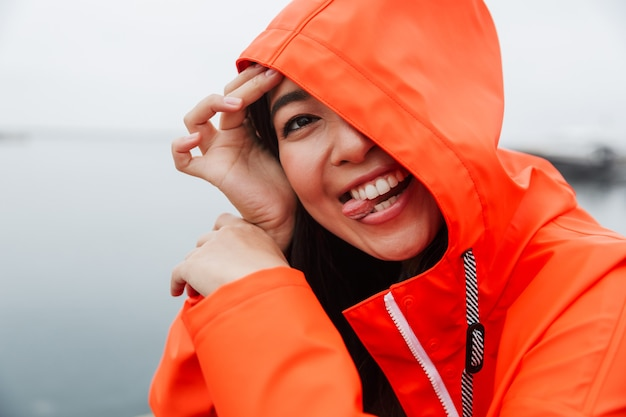 Smiling funny young asian woman wearing raincoat spending time outdoors walking at the coastland, wearing a hood