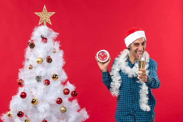 サンタクロースの帽子をかぶって面白い若い男を笑って、ワインのグラスを上げて、赤いクリスマスツリーの近くに立っている時計を保持します