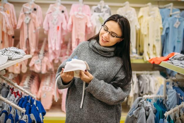 笑顔の未来の母親が赤ちゃんの帽子を選ぶ