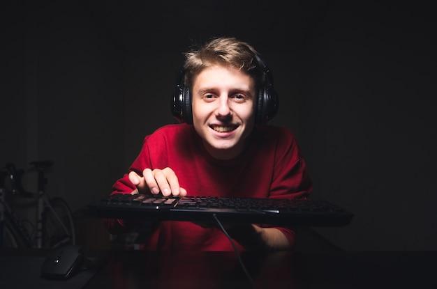 웃는 게이머는 어두운 방을 배경으로 비디오 게임을하고 키보드를 손에 들고