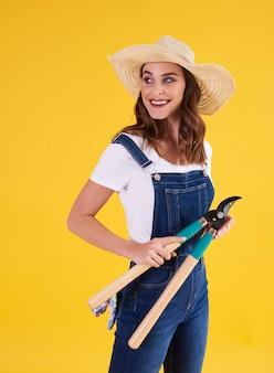 Sorridente giardiniere che tiene tagliasiepi in studio shot