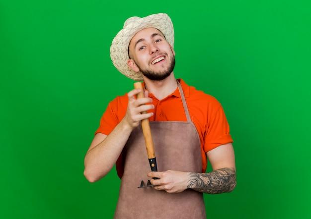 원예 모자를 쓰고 웃는 정원사 남자는 갈퀴를 거꾸로 보유하고 있습니다.