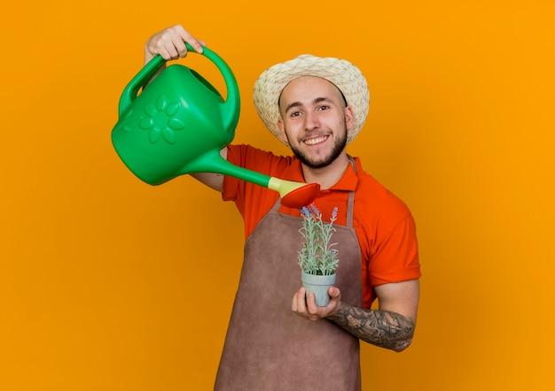 Sorridente giardiniere uomo che indossa il cappello da giardinaggio tiene annaffiatoio fingendo di annaffiare la pianta in vaso di fiori