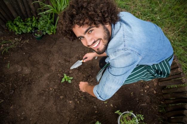 Улыбающийся садовод за пределами теплицы