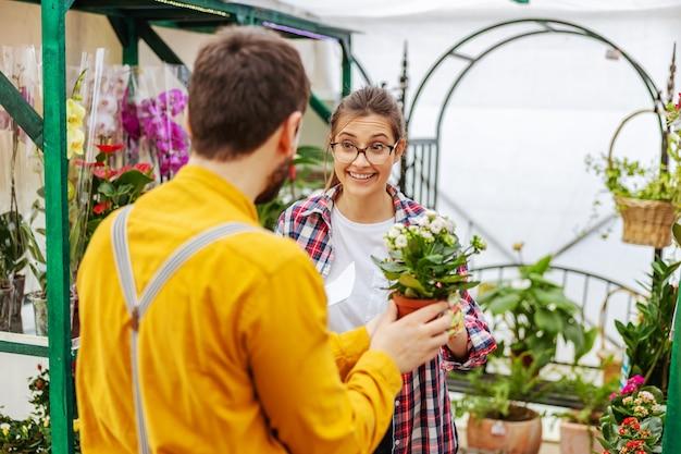 温室に立っている間、顧客に花を売る笑顔の庭師。