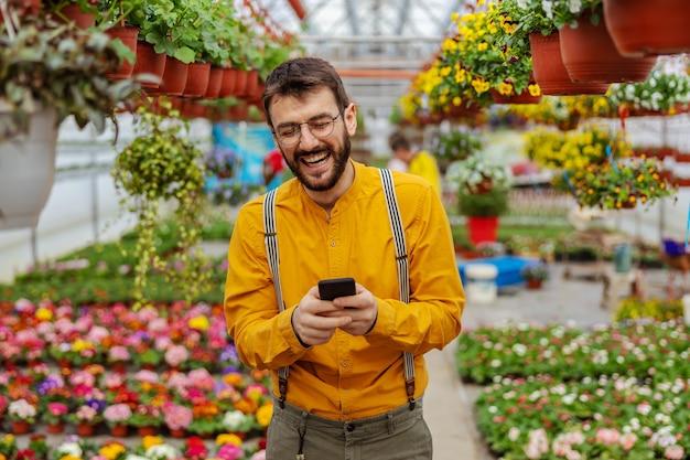 温室に立ってスマートフォンで顧客から注文を受けている庭師の笑顔。