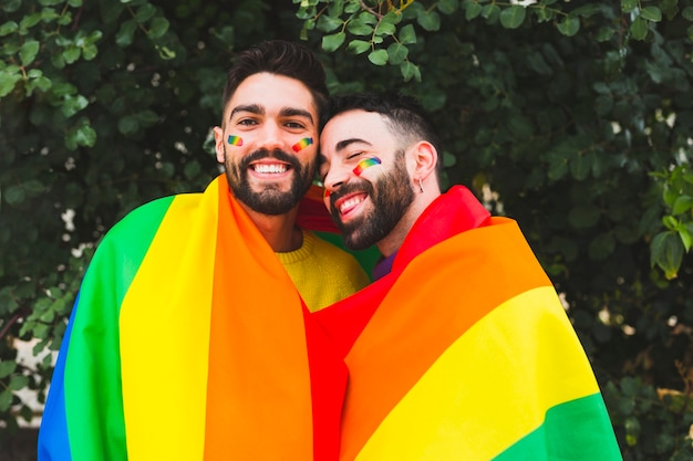 Smiling gay couple covering rainbow flag