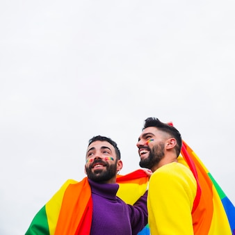 Smiling gays with rainbow flag looking in same direction