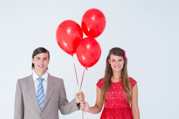 Smiling geeky couple holding red balloons