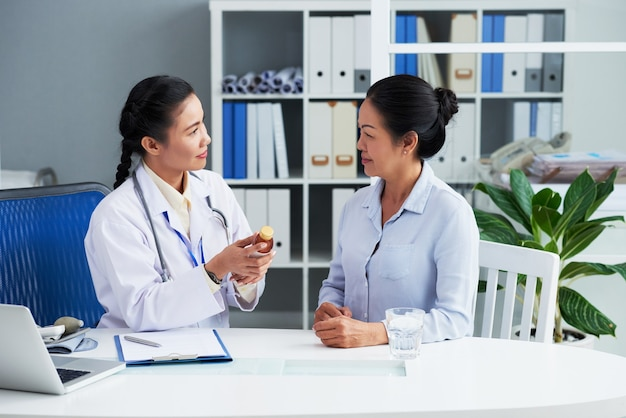 Smiling general practitioner recommending liquid remedy to senior patient