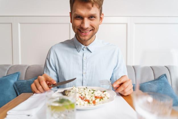 신선한 샐러드와 함께 테이블에 앉아있는 동안 포크와 나이프를 들고 셔츠에 웃는 신사