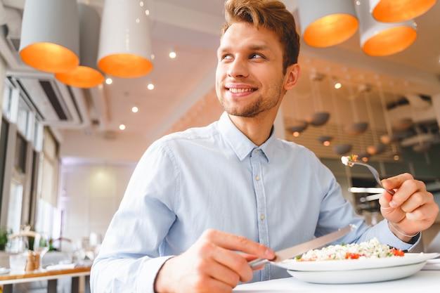 맛있는 신선한 샐러드와 함께 카페 테이블에 앉아 멀리 바라보는 웃는 신사