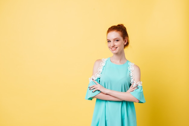Smiling ginger girl in dress posing with crossed arms and looking