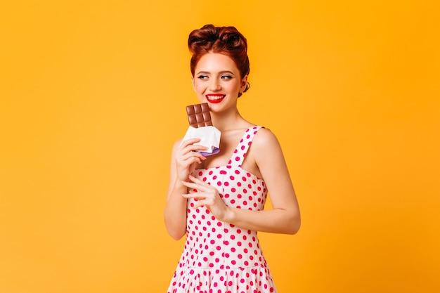 초콜릿을 먹고 웃는 생강 소녀. 노란색 공간에 고립 된 폴카 도트 드레스에 핀 업 여자의 스튜디오 샷.