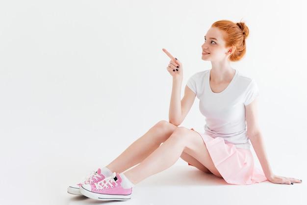 Улыбающаяся рыжая девушка сидит на полу и указывая прочь