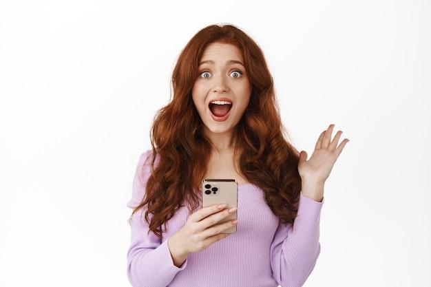 Улыбающаяся рыжая женщина, держащая смартфон на белом