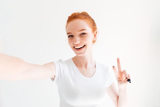 T- 셔츠 만들기 selfie 및 평화 제스처를 보여주는 웃는 생강 여자