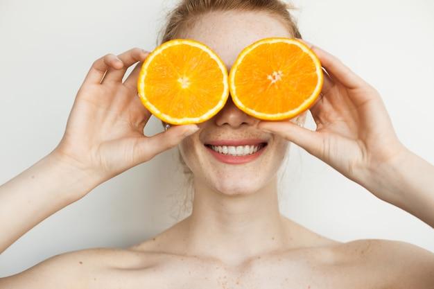 そばかすのある笑顔の生姜の女性は、白い壁にポーズをとってスライスしたオレンジで彼女の顔を覆っています