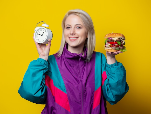 Smiling girl in 80s clothes style with burger and alarm clock