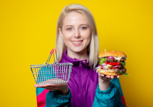 Smiling girl in 80s clothes style with burger and supermarket basket