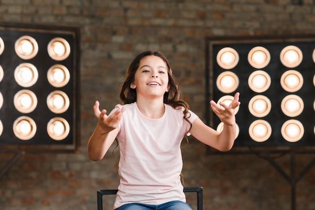 バックグラウンドでステージライトとスタジオで演技する笑顔の女の子