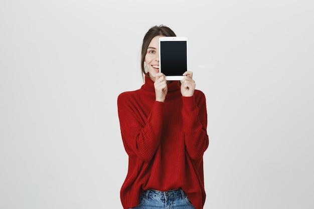 Улыбающаяся девушка рекламирует приложение, показывает экран цифрового планшета
