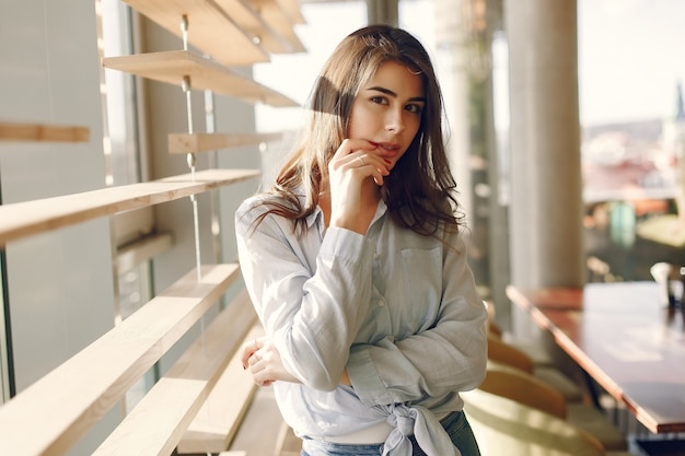 Smiling girl in a blue shirt standing near window