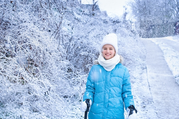 Smiling girl in blue winter clothes with scandinavian walking sticks stands in the park.