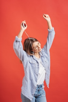 Smiling girl in casual clothes and earphones dancing moving hands.