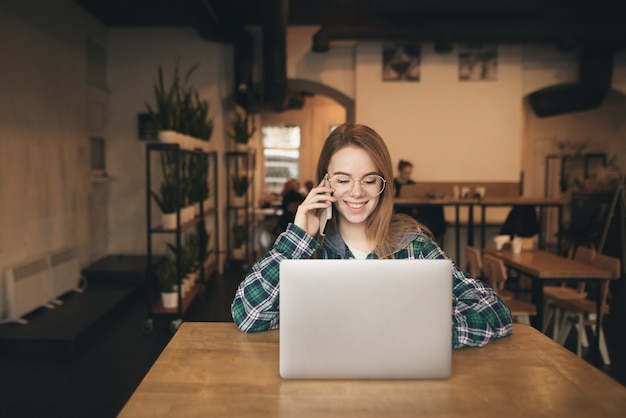 Smiling girl in casual clothes speaks by telephone and uses the internet on a laptop in a cozy cafe, looks at the screen and smiles