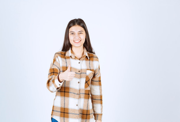 Smiling girl in checkered shirt showing a thumb up .