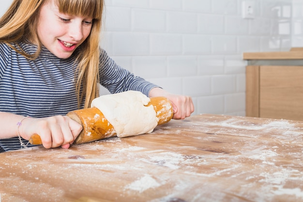 Smiling girl cooking dough in kitchen