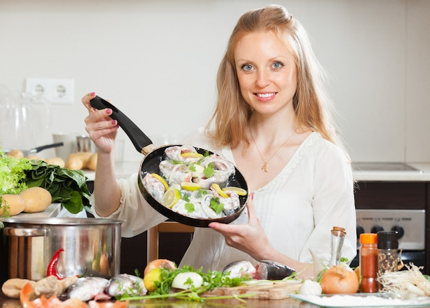 Smiling girl cooking fish with lemon