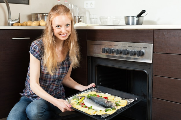Smiling girl cooking raw fish in oven
