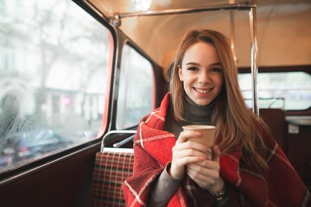 Улыбающаяся девушка в пледе с чашкой кофе в руках сидит в кафе