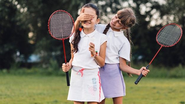 Smiling girl covering her friend eyes holding badminton