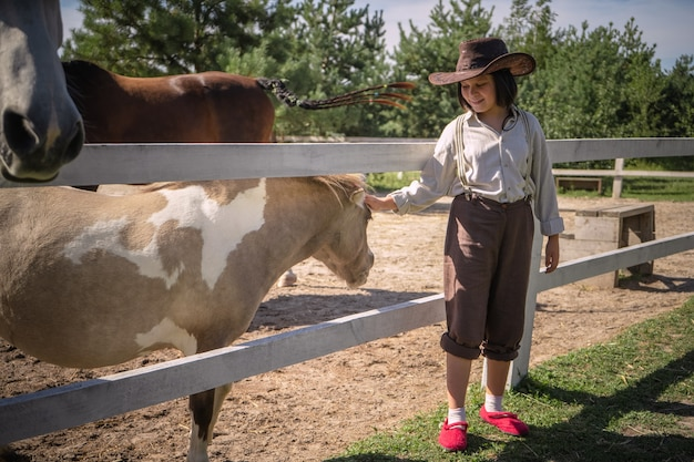 Smiling girl in cowboy clothes strokes little pony in paddock on sunny summer day. taking care of animals concept.