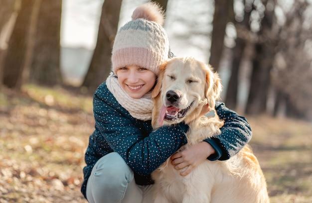 Smiling girl cuddling cute dog