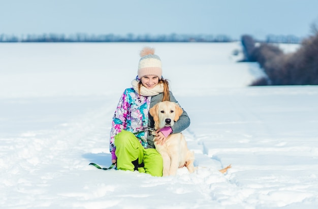 Улыбающаяся девочка, обнимающая прекрасную собаку на заснеженном поле