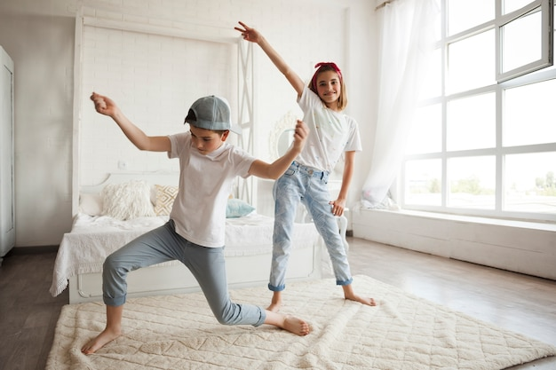 Smiling girl dancing with her little brother at home
