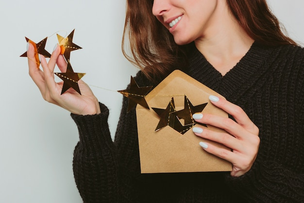 A smiling girl in a dark sweater takes out a garland of gold stars from a craft envelope. gray background