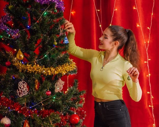 Smiling girl decorates a christmas tree