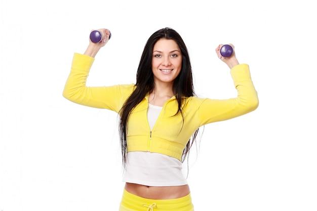 Улыбающаяся девушка делает фитнес-тренировки на белом