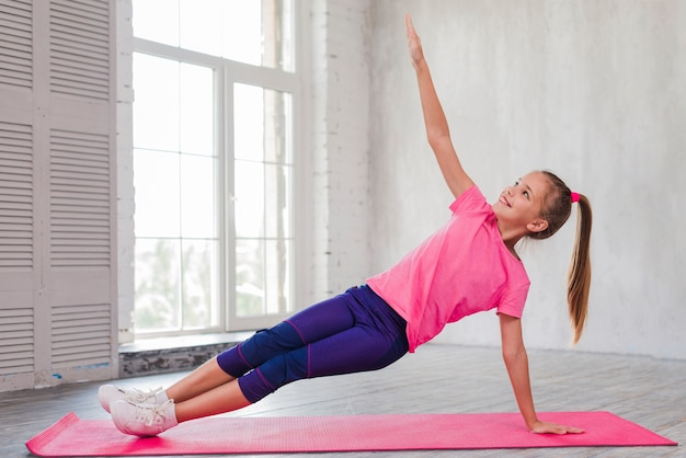 Smiling girl doing stretching exercise in the gym