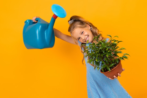 Smiling girl in a dress holds a plant and a watering can on an orange wall